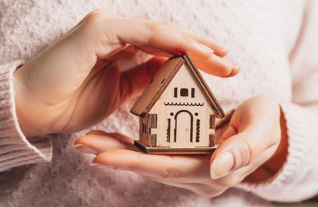 Donna che tiene una casa in legno con le sue mani con il sole su uno spazio rosa chiaro