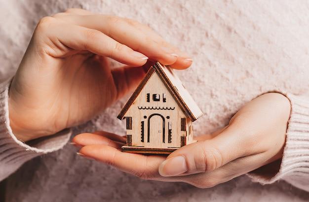 Donna che tiene una casa di legno con le mani con il sole su una superficie rosa chiaro. dolce casa