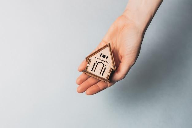 Donna che tiene una casa in legno con le sue mani