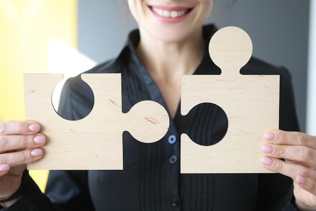 Donna che tiene i dettagli di puzzle di legno nel suo primo piano delle mani