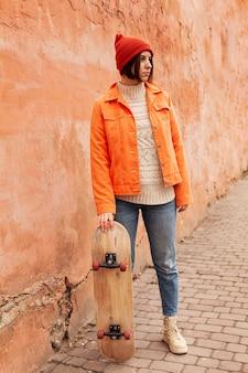 Donna che mantiene uno skateboard in legno