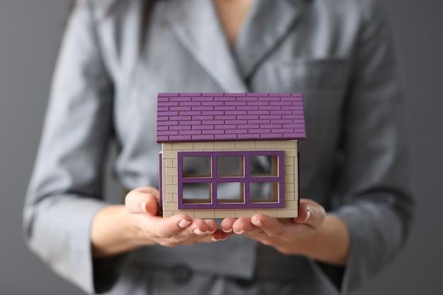 Donna che tiene casa giocattolo di legno nelle sue mani concetto di assicurazione sulla casa del primo piano
