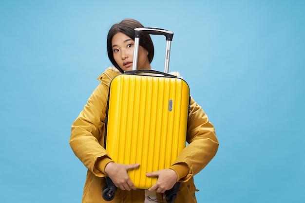 Donna che tiene la valigia gialla bagaglio viaggio vacanza aeroporto passeggero luggage