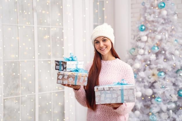 La donna tiene 3 regali di natale nelle sue mani