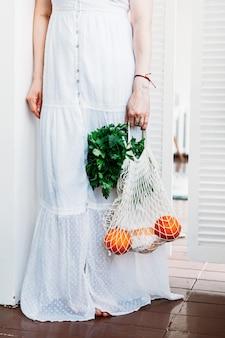 La donna tiene una borsa con frutta e verdura fresca di cibo
