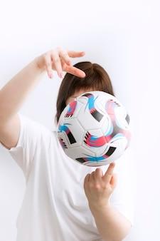 La donna tiene la palla in mano. avvicinamento. allenamento sportivo con la palla. isolato su sfondo bianco. palla nelle mani di un allenatore di calcio