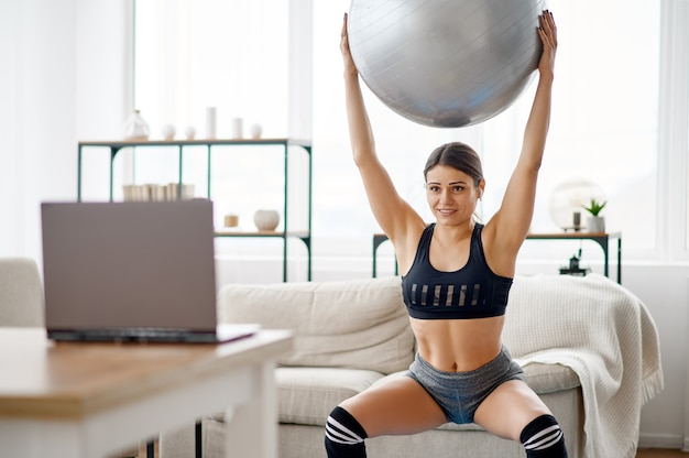La donna tiene la palla, formazione online di pilates al computer portatile. persona di sesso femminile in abbigliamento sportivo, allenamento sportivo internet, interno della stanza