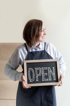 La donna tiene il bordo con testo aperto. il lavoratore in grembiule mostra l'apertura del caffè o del mercato.