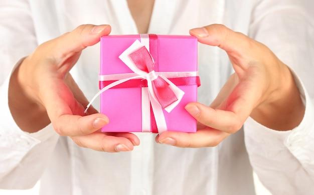 La donna tiene la scatola con il regalo sul primo piano bianco del fondo