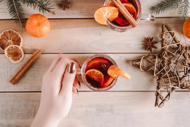 La donna tiene la tazza di vin brulé caldo nelle sue mani. bevanda riscaldante invernale per le vacanze.