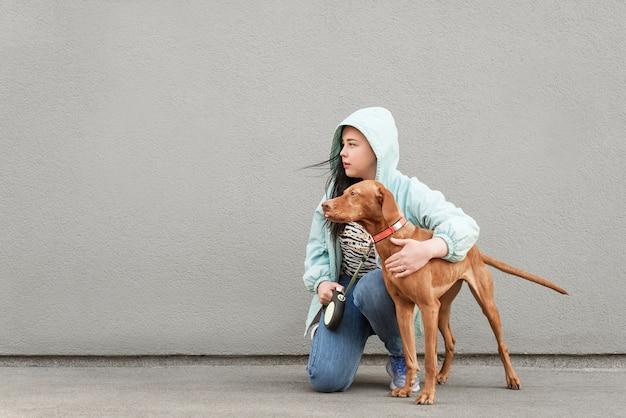 La donna tiene un cane al guinzaglio, si siede sullo sfondo di un muro grigio e guarda di lato.