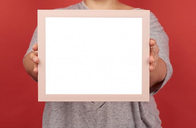 La donna tiene una cornice rosa vuota su uno sfondo rosso
