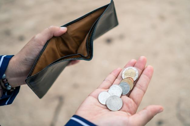 La donna tiene in mano una borsa vuota e le monete significano il problema finanziario dei soldi o il fallimento senza lavoro, rotto dopo il giorno di paga della carta di credito senza lavoro.