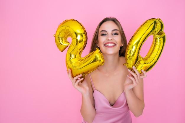La donna tiene palloncini di alluminio sotto forma di numeri con sconti del venti percento sulle vendite e cashback