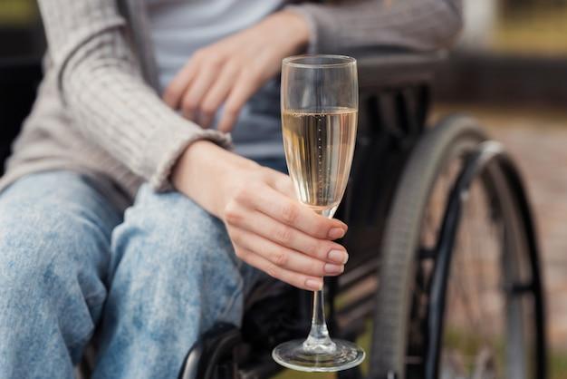 La donna tiene in mano un bicchiere di champagne.