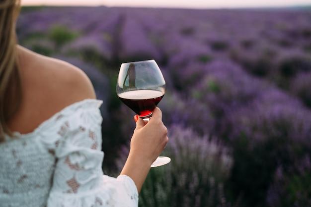 La donna tiene un bicchiere di vino nel campo di lavanda