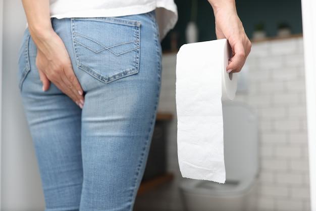 La donna tiene la mano sul prete nell'altra carta igienica e sta di fronte all'umiliato