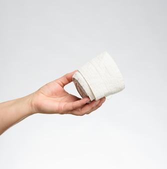 La donna tiene in mano una benda elastica bianca per il corpo