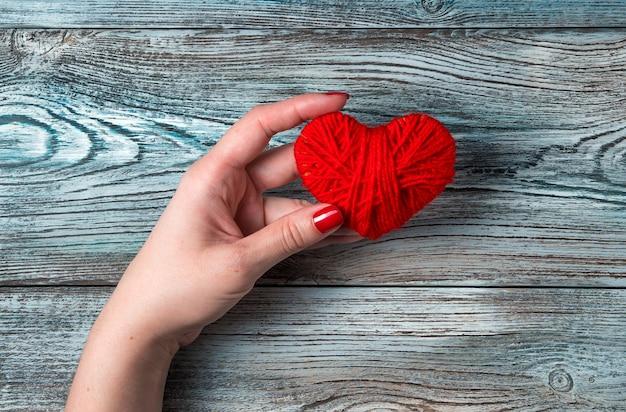 Una donna tiene un cuore in una mano su un tavolo di legno grigio-blu.