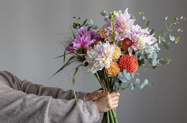 Una donna tiene in mano una composizione floreale festiva con fiori di crisantemo luminosi, un bouquet festivo.