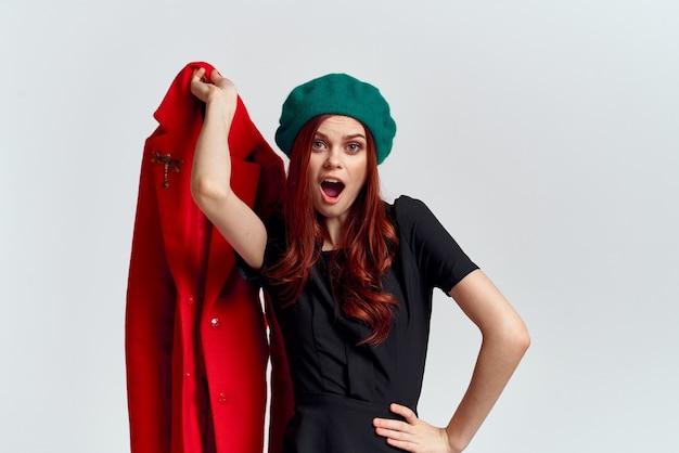 Una donna tiene in mano un cappotto rosso e una maglietta scura cappello verde ritagliata vista di uno sfondo chiaro.