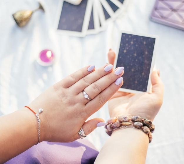 La donna tiene la mano con unghie viola su carta dei tarocchi su superficie bianca con taccuino e candela, vista dall'alto.