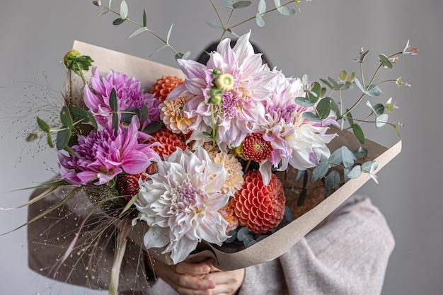 Una donna tiene tra le mani un grande bouquet festivo con crisantemi e altri fiori, primo piano.