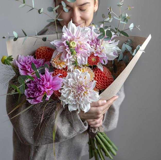 Una donna tiene tra le mani un grande bouquet festivo con crisantemi e altri fiori.