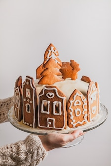 La donna tiene la torta fatta in casa con la casa di città di pan di zenzero, l'albero di natale e la renna su supporto di vetro, con spazio per le copie.