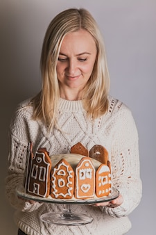 La donna tiene una torta fatta in casa con facciate di case di città di pan di zenzero, un albero di natale e renne su un supporto di vetro glass