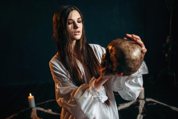 La donna tiene in mano teschio umano, magia oscura, strega