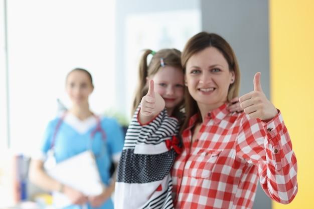 La donna tiene la bambina tra le braccia e mostrano il gesto del pollice in alto sullo sfondo è dottore