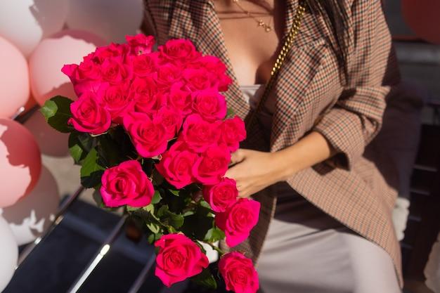 La donna tiene il mazzo di lusso delle rose rosse.