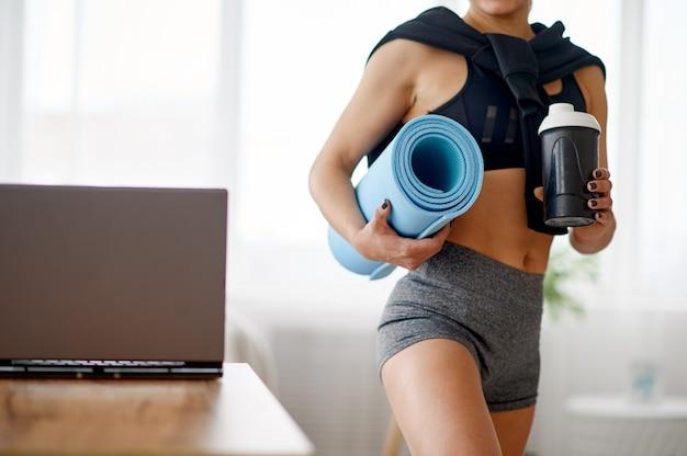 La donna tiene la stuoia, allenamento fitness online. persona di sesso femminile in abbigliamento sportivo, allenamento sportivo internet, interno della stanza