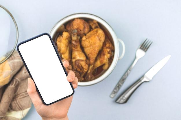 La donna tiene il telefono cellulare con lo schermo del modello con il pollo fritto domestico dell'alimento arrosto in una casseruola, menu sano per la foto di concetto del ristorante, schermo bianco, foto dello spazio della copia