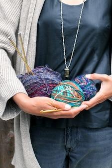 La donna tiene palline luminose multicolori di filato di lana per maglieria. filati per maglieria, ferri da maglia, matasse. bellissimi colori per lavorare a maglia. concetto di lavoro a maglia creativo fatto a mano.
