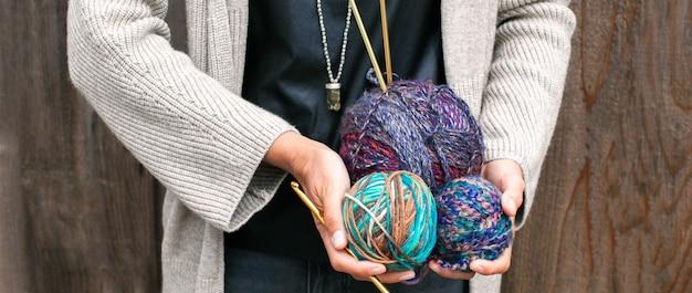 La donna tiene palline multicolori di filato di lana per lavorare a maglia matasse di aghi di filato per maglieria