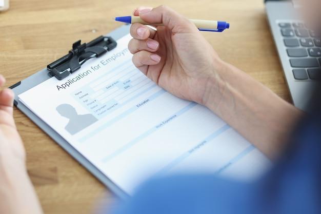 La donna tiene la penna e prevede di compilare il modulo di curriculum per suggerimenti sul lavoro per scrivere un concetto di curriculum