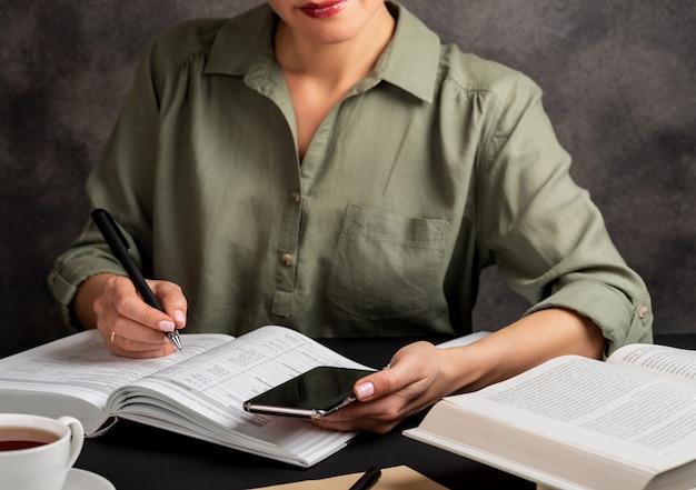 La donna tiene il telefono in mano, scrive e studia a casa