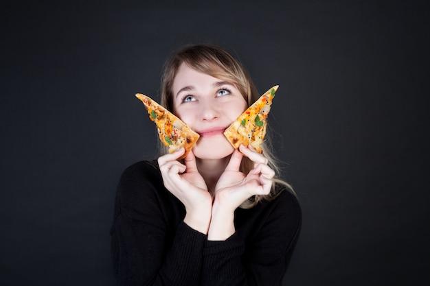 Una donna tiene fette di pizza, lanciandole come coltelli. foto di concetto per la pubblicità della pizza.