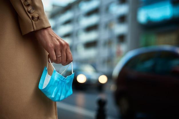 La donna tiene la maschera protettiva in mano alla via della città