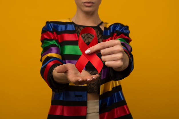 La donna tiene il nastro rosso per sensibilizzare la giornata mondiale contro l'aids 1 dicembre