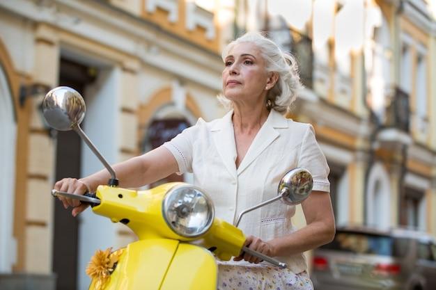 La donna tiene il volante del motorino.