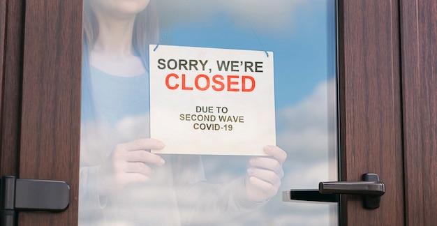 La donna tiene il segno dietro la porta di vetro del negozio
