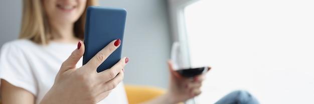 La donna tiene in mano smartphone e bicchiere di vino rosso