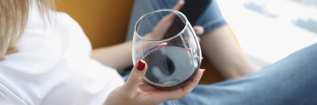 La donna tiene in mano smartphone e bicchiere di vino