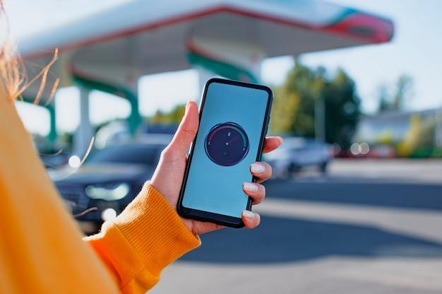 La donna tiene uno smartphone con un misuratore di carburante digitale sullo schermo sullo sfondo di una stazione di servizio e di un'auto.