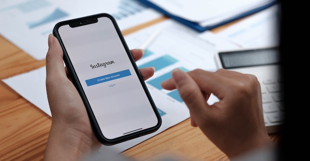 Una donna tiene lo smartphone con l'applicazione instagram sullo schermo. instagram è un'app di condivisione di foto per smartphone.