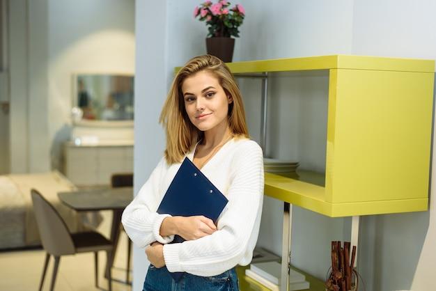 Una donna tiene in mano una cartella per tablet per documenti. una bella signora è in piedi a casa e guarda la telecamera. ufficio a casa.