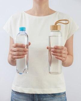 La donna tiene due bottiglie di plastica e vetro con acqua naturale fresca pulita contro il tavolo grigio chiaro, lo spazio della copia. concetto di rifiuti zero. utilizzando una bottiglia di vetro riutilizzabile invece di plastica monouso.